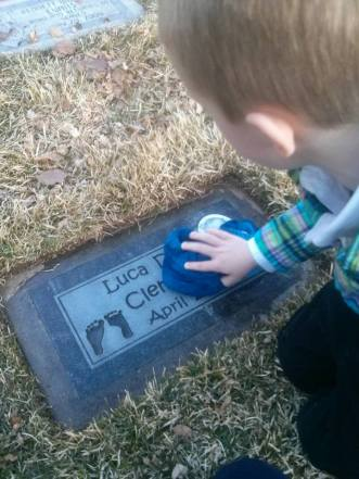 My second son wipes away dirt and grass from his little brother's headstone.